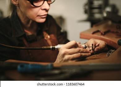 Senior female jewelry maker polishing a product at her workbench. Jewelry designer polishing a bracelet at workshop.