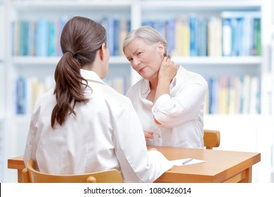 Senior female patient consulting her physician or doctor on account of chronic neck pain caused by fibromyalgia