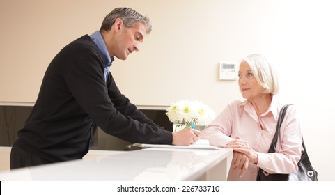 Senior female patient at hospital reception desk with man in 40s collecting personal data.