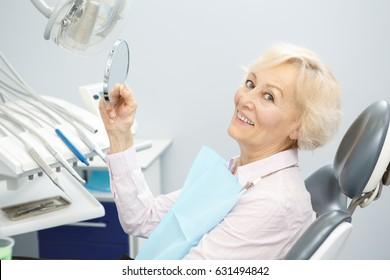 Paciente feminino sênior sorrindo para a câmera segurando um espelho sentado em uma cadeira dentária na clínica dentes sorriso exame procedimento de tratamento felicidade saudável vitalidade medicina pensionista antiguidade