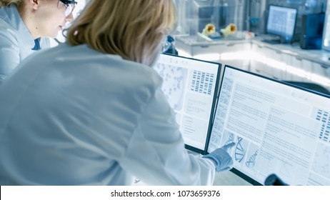 Senior Female Scientist Discusses Scientific Data with Her Laboratory Assistant. They're looking at Two Displays in a Modern Laboratory.