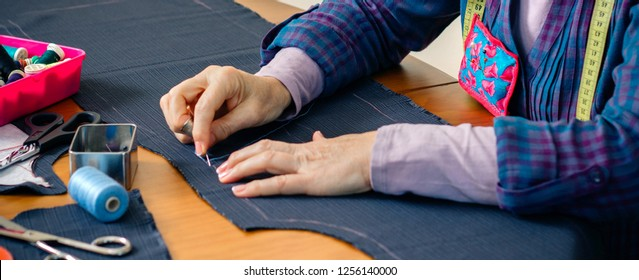 Senior female seamstress sewing cloth to make a garment in her workshop