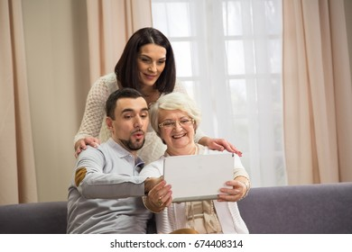 Senior female with tablet and younger generation couple
