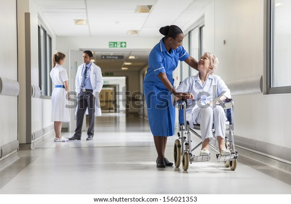 Senior female woman patient in wheelchair sitting in hospital corridor with African American female nurse and doctor