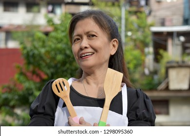 Senior Filipina Female Cook And Happiness With Utensils