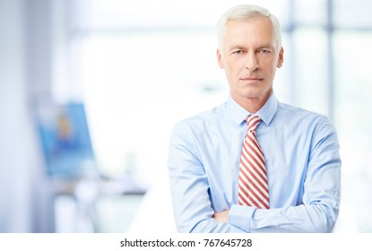 A senior financial consultant businessman standing in his office with arms crossed.