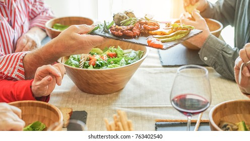 Senior firends having lunch at home - Mature people eating bbq vegetables,fresh salad and drinking red wine - Healthy food and joyful elderly active lifestyle concept - Focus on man hand holding dish
