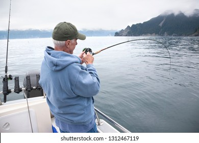 A senior fisherman fights a fish in the ocean near Seward, Alaska