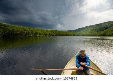 Senior fisherman rowing in a boat on a lake Mikkeljavre in Norway