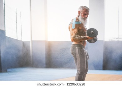 Senior fitness man doing biceps curl exercises inside old gym - Fit mature male training with dumbbells in wellness club center - Body building and sport healthy lifestyle concept