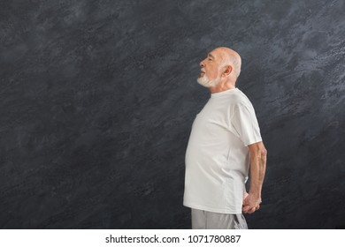 Senior fitness man warmup training indoors. Sporty mature guy makes aerobics exercise, stretching back. Active lifestyle and healthcare in any age, side view, copy space