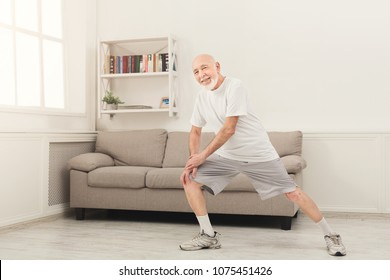 Senior fitness man warmup training at home. Sporty mature guy makes aerobics exercise, stretching legs. Active lifestyle and healthcare in any age, copy space