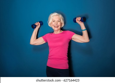 senior fitness woman training with dumbbells isolated on blue