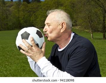 Senior football player kissing his ball