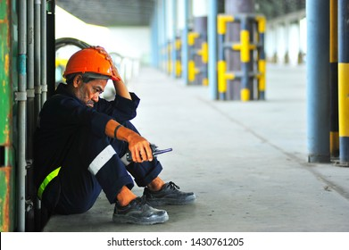 Senior foreman sitting on the floor in the warehouse and hopelessly with sad feeling.