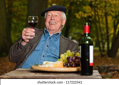 Senior french man enjoying red wine and cheese outdoors in autumn forest.