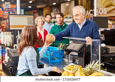 Senior as a friendly customer when paying at the supermarket cashier