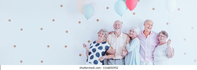 Senior friends with balloons enjoying retirement, posing together at a birthday party on a white wall and copy space.