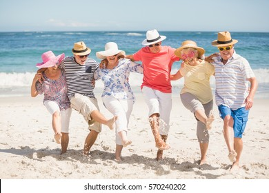 Senior friends dancing on the beach on a sunny day