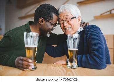 senior friends drinking beer and having fun in bar