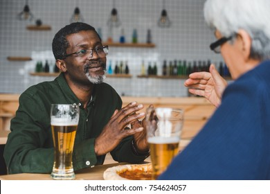 senior friends having discussion at bar while drinking beer with pizza