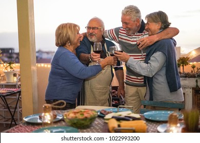 Senior friends having fun doing barbecue dinner in terrace outdoor - Mature people dining and laughing togheter - Focus on left man face - Joyful elderly lifestyle, love and friendship concept