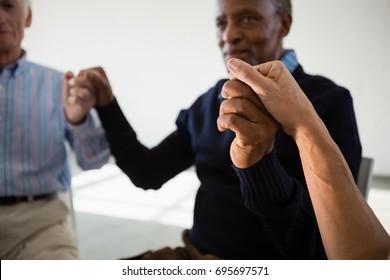 Senior friends holding hands in retirement centre