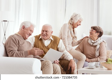 Senior friends are laughing and talking together while using laptop