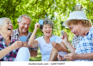 Senior friends playing cards in a tournament at leisure in the garden or park
