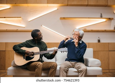 senior friends playing music with acoustic guitar and harmonica while sitting on couch