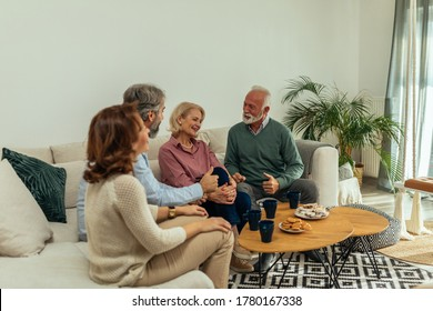 Senior friends sitting in the living room, socializing and enjoying coffee time