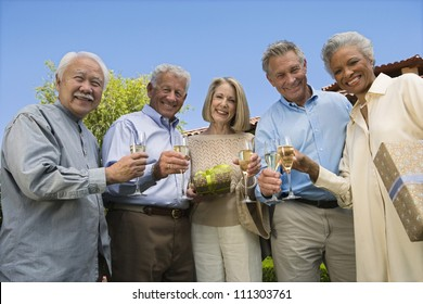 Senior friends standing together with champagne glass