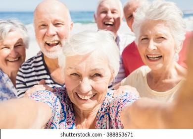 Senior friends taking selfie on the beach