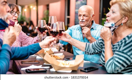 Senior befreunde, die in der Bar des Restaurants mit Geoffener Gesichtsmaske Wein toasten - Neues normales Lifestyle-Konzept mit glücklichen, reifen Leuten, die sich auf der Gartenparty amüsieren - Warm-Filter mit Fokus auf Glatschmann