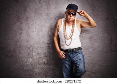 Senior gangster in baggy hip-hop clothes looking at the camera and leaning against a rusty gray wall