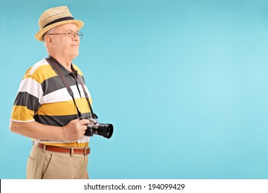 Senior gentleman with camera posing on blue background