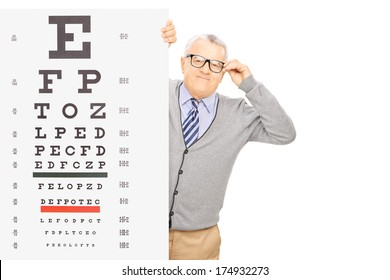 Senior gentleman with glasses standing behind eyesight test isolated on white background