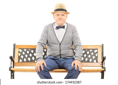 Senior gentleman with hat seated on bench looking at camera isolated on white background