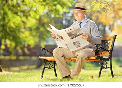 Senior gentleman with hat sitting on a wooden bench and reading a newspaper in a park