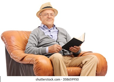 Senior gentleman holding a book seated in an armchair and looking at the camera isolated on white background