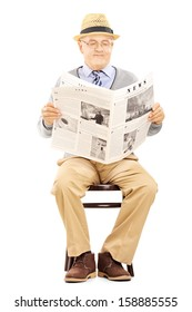 Senior gentleman reading newspaper and sitting on a wooden chair isolated on white background