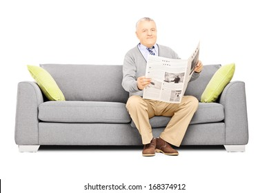Senior gentleman sitting on a modern sofa with newspaper looking at camera isolated against white background