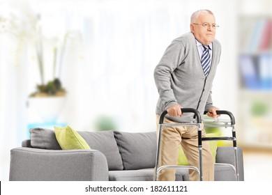Senior gentleman walking with walker indoors