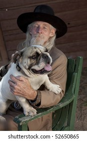 A senior gentleman wearing a western style suit and cowboy hat is sitting in a chair with a bulldog. Vertical shot.
