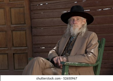 A senior gentleman wearing a western style suit and cowboy hat is sitting in a chair. Horizontal shot.