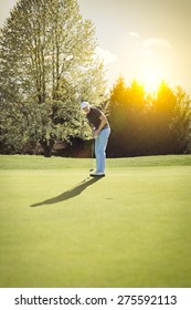 Senior golf player putting on green at sunset, with blank copyspace.