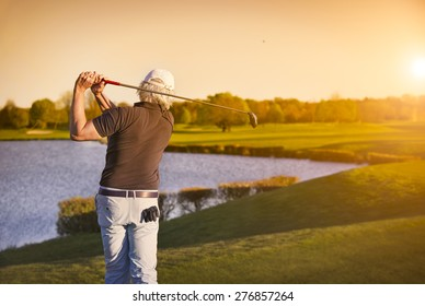 Senior golf player shooting ball at sunset, with lake in background.