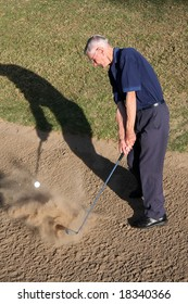 Senior golfer hitting ball out of golf sand trap