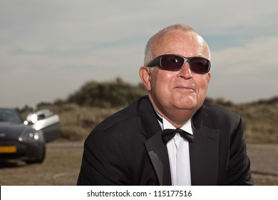 Senior good looking happy relaxed retired man with his sports car in dune landscape with cloudy sky. Wearing smoking suit and glasses. Classy different man.