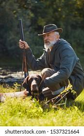 Senior good-looking hunter with his tracker dog in hunt on wild ducks. Sitting near lake, wearing hat, holding gun